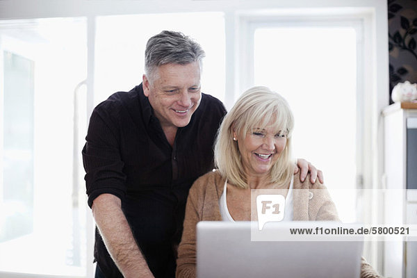 Fröhliches reifes Paar mit Laptop zu Hause