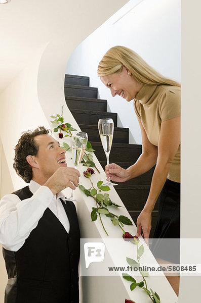 Paar hält Sektgläser im Treppenhaus dekoriert mit roten Rosen