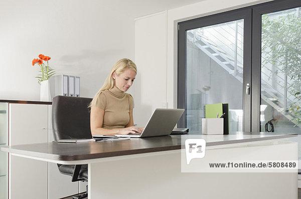 Geschäftsfrau benutzt einen Laptop am Schreibtisch