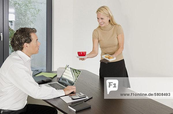 Frau serviert Geschäftsmann am Schreibtisch Kaffee und Gebäck