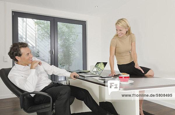 Geschäftsmann und Geschäftsfrau im Büro lächeln sich an