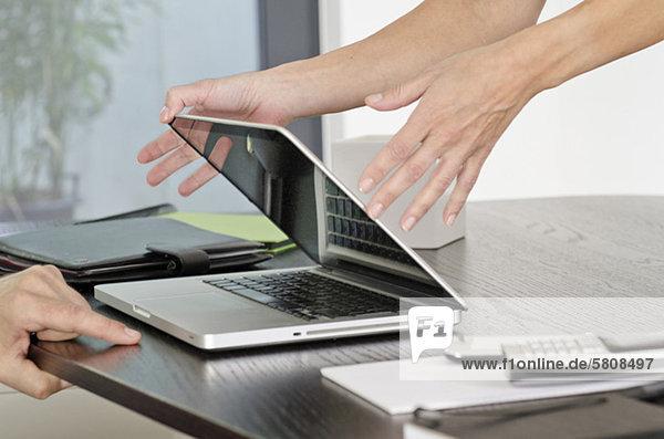 Woman closing laptop at desk