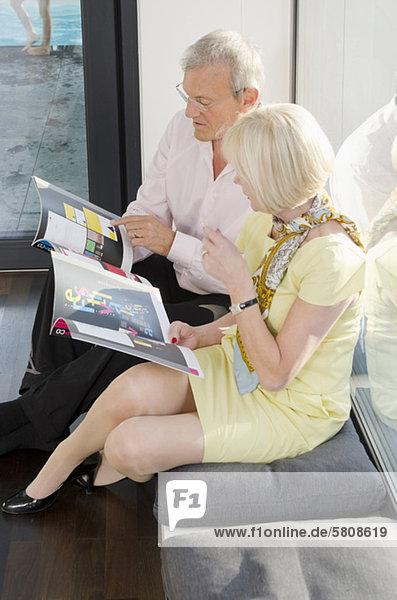 sitzend Senior Senioren sehen Fenster Zeitschrift