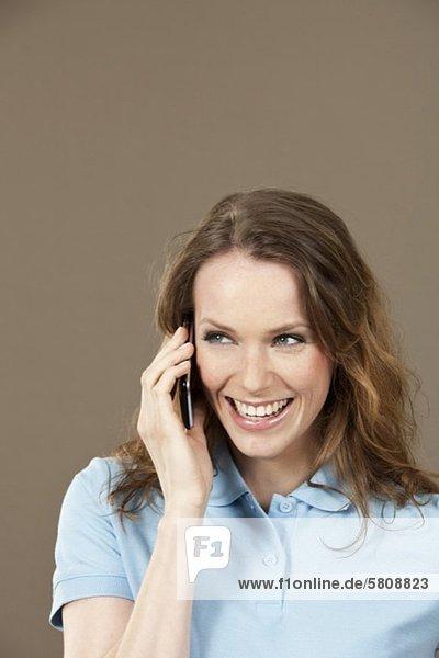 Fröhliche junge Frau telefoniert mit Handy