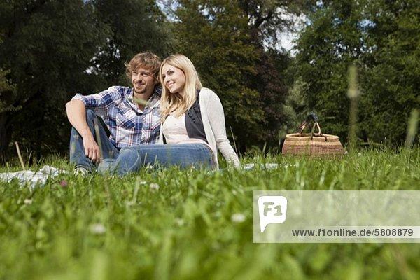Entspanntes junges Paar auf einer Decke auf einer Wiese