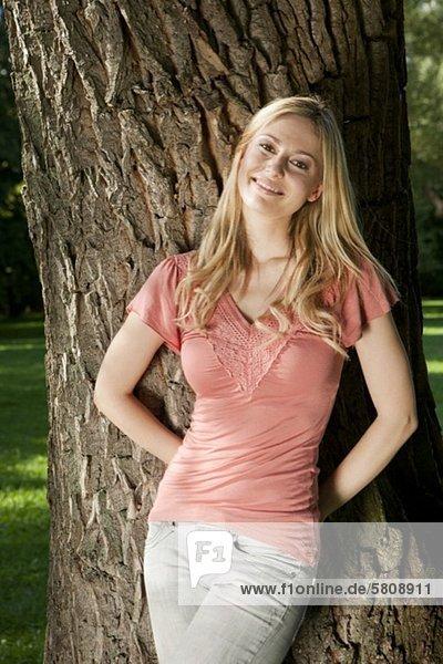 Lächelnde junge Frau im Freien lehnt an einem Baumstamm