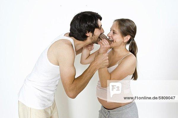 Fröhlicher Mann und schwangere Frau essen Schokolade