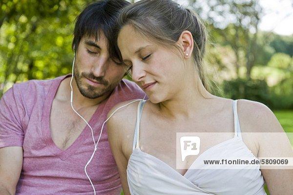 Mann und Frau hören Musik mit geschlossenen Augen