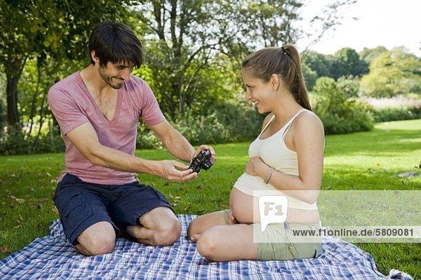Mann fotografiert schwangere Frau im Park