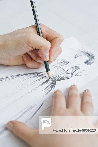 Schneiderin zeichnet auf einen Skizzenblock