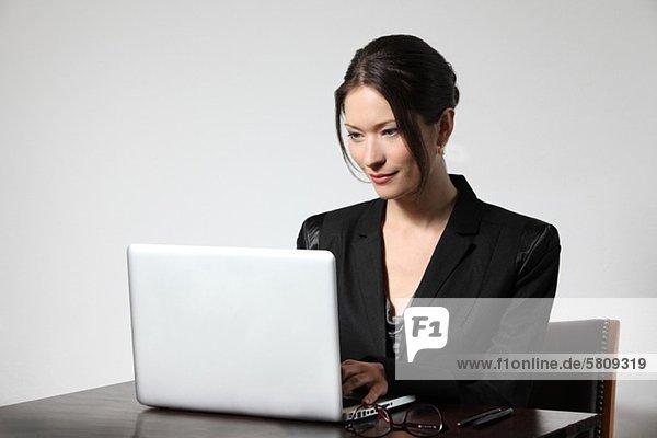 Geschäftsfrau arbeitet am Laptop am Schreibtisch