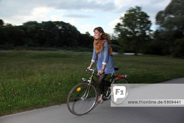Fröhliche junge Frau fährt Fahrrad