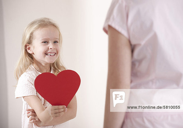 Smiling girl holding heart in front of her mother