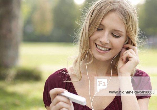 Junge Frau mit MP3-Player im Freien