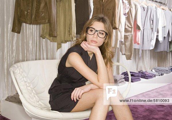 Junge Frau sitzt in einer Boutique