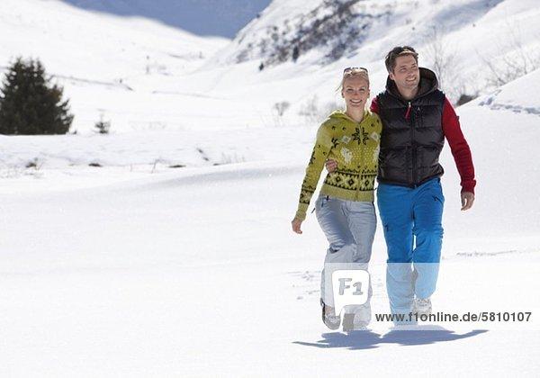 Lächelndes Paar geht in Winterlandschaft spazieren