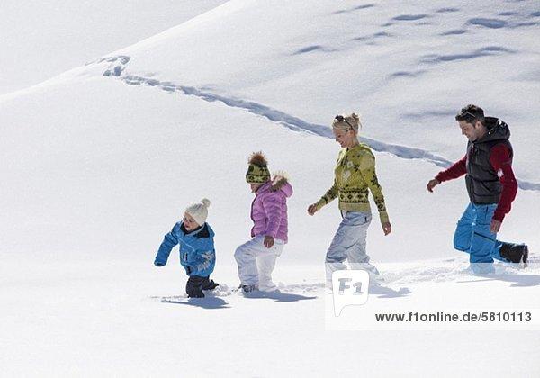 Familie geht durch Schnee Familie geht durch Schnee