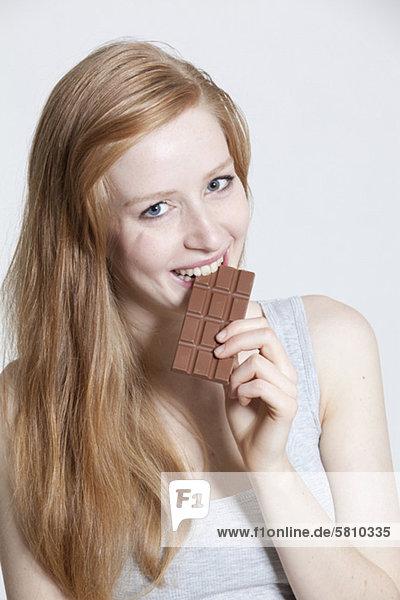Rothaarige junge Frau isst Schokolade Rothaarige junge Frau isst Schokolade