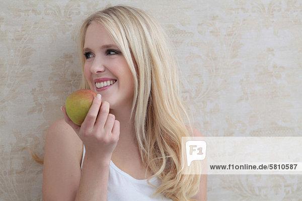 Lächelnde junge Frau isst einen Apfel