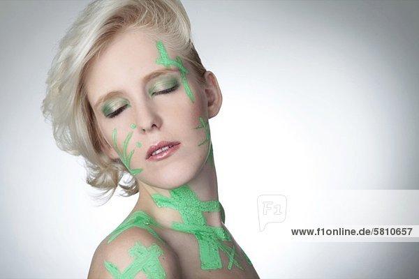 Blonde junge Frau mit bemaltem Gesicht und Körper