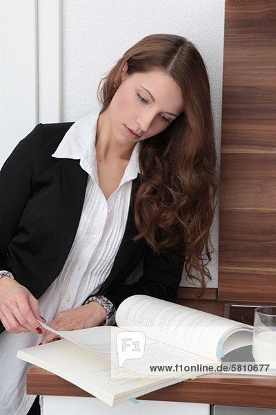 Brünette Geschäftsfrau liest ein Buch