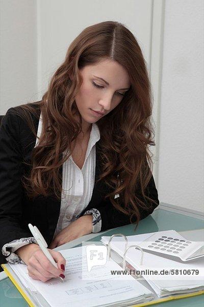 Brunette businesswoman working on file