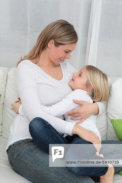 Mutter und Tochter kuscheln auf der Couch