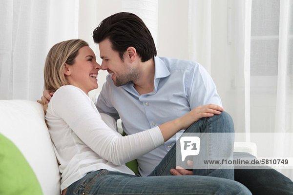 Fröhliches Paar umarmt sich auf der Couch