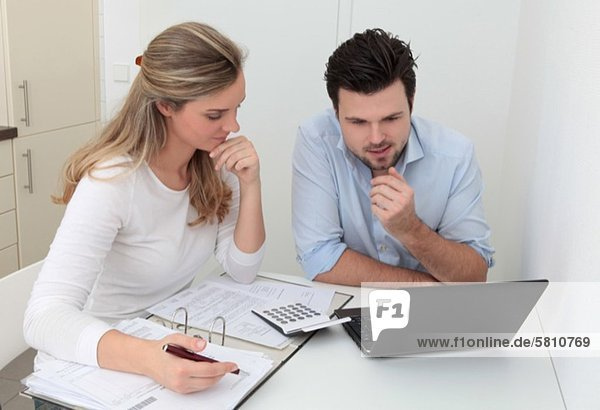 Man and woman sitting at table with file  calculator and laptop