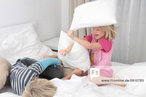 Bruder und Schwester bei einer Kissenschlacht im Bett