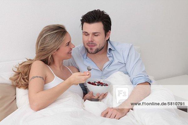 Paar isst eine Schale mit Beeren im Bett