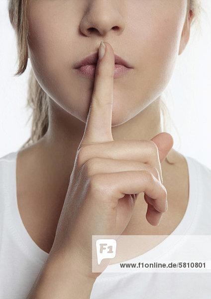 Junge Frau legt ihren Finger auf den Mund