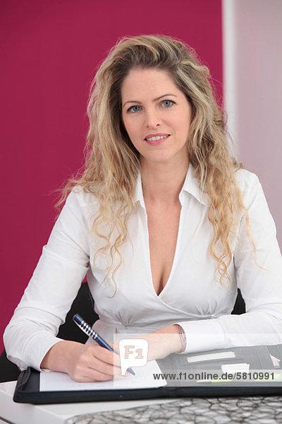 Geschäftsfrau mit Kugelschreiber und Mappe im Büro