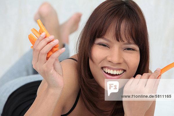 Fröhliche junge Frau hält Möhren