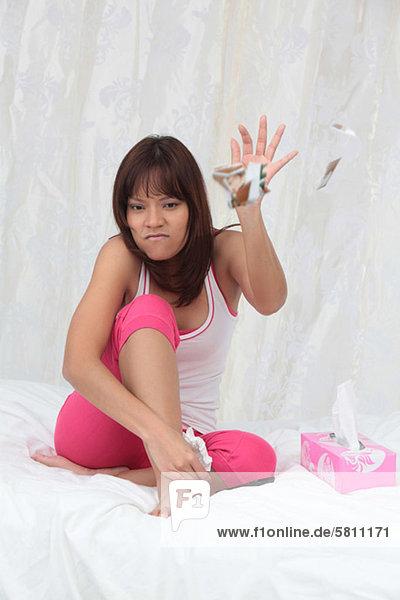 Wütende junge Frau sitzt auf dem Bett