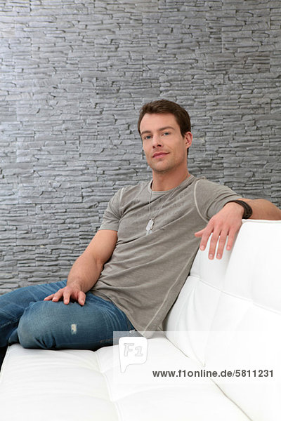 Brunette man in T-shirt sitting on couch