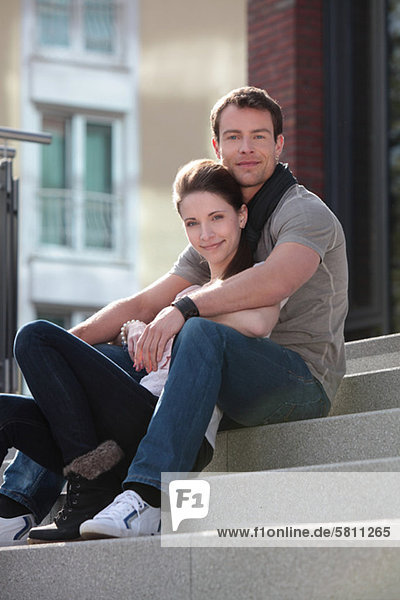 Happy couple sitting on stairs outdoors