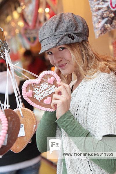 Fröhliche Frau mit Lebkuchenherz auf einem Jahrmarkt