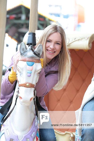 Fröhliche Frau auf einem Karussell