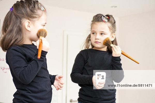 Mädchen schaut in den Spiegel und trägt Rouge auf