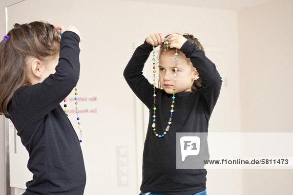 Mädchen mit Halskette schaut in den Spiegel