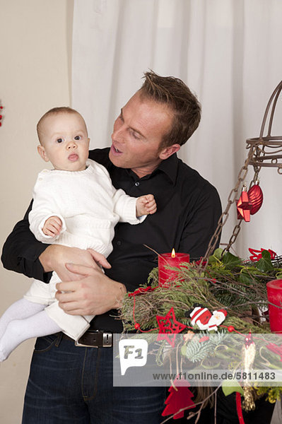 Vater hält Baby am Weihnachtskranz