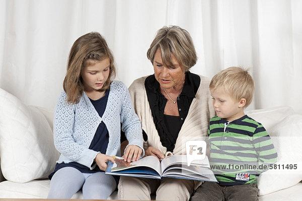 Großmutter liest Enkeln aus einem Buch vor