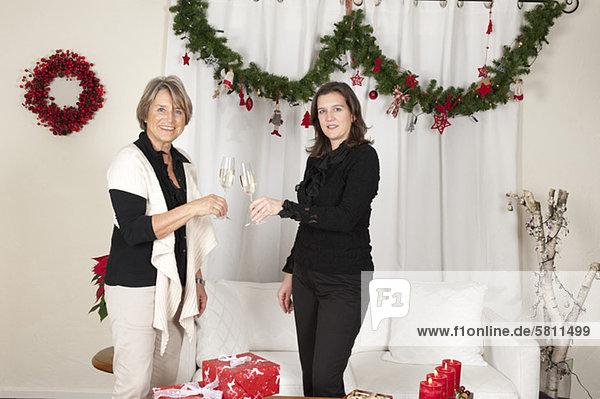 Mutter und erwachsene Tochter stoßen zu Weihnachten mit Sektgläsern an