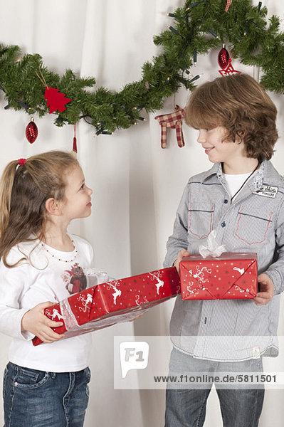 Bruder und Schwester überreichen Weihnachtsgeschenke