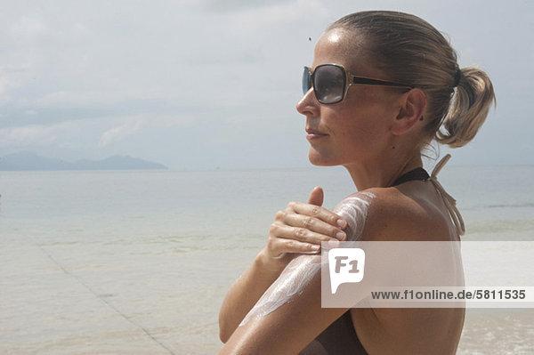 Frau am Strand trägt Sonnencreme auf  Thailand
