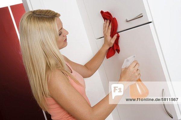 Junge Frau reinigt den Küchenschrank