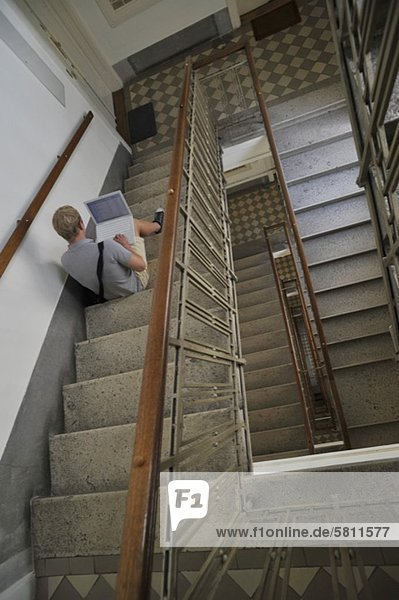 benutzen Mann Notebook Treppenhaus jung