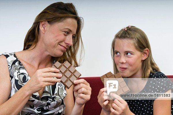 Mutter und Tochter essen Schokolade