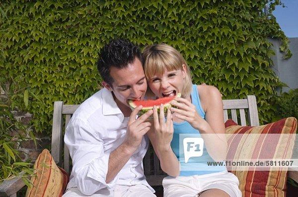 Junges Paar isst eine Wassermelone im Freien